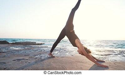 pratiquer, eka, femme, mouvement, pada, time., mukha, jeune, mer, plage, seul, yoga, lent, adho, svanasana, coucher soleil