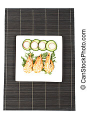 Prawns on the white plate over a bamboo mat. Shallow depth ...