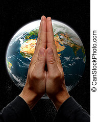 praying hands in front of earth concept