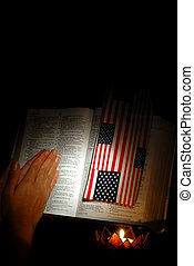 Praying hands next to a Bible with US flag