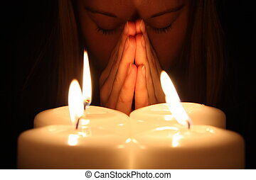 Young woman prays over alight candles in a darkness