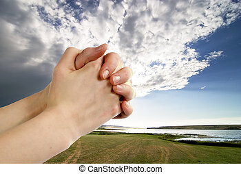 Prayer - A pair of hands in a praying position set against a...