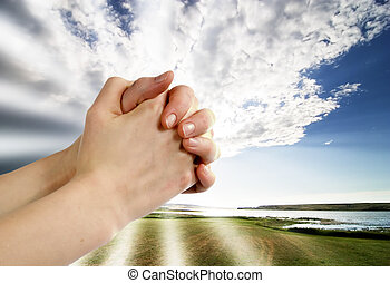 A pair of hands in a praying position set against a beautiful prairie lake landscape