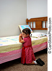 Prayer - A young girl kneeling down saying a prayer