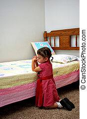 Prayer - A young girl kneeling down saying a prayer