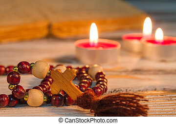 Prayer beads rosary with wooden cross closeup.
