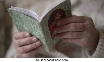 Prayer book in old woman's hands. Slowly