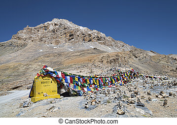 Prayer flags and stone pyramids at the foot of jagged mountain