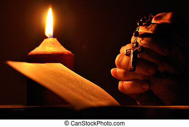 Still life with candle, prayer book and prayer hands