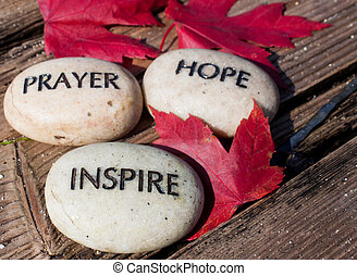 three large beige rocks inscribed with the words hope, inspire and pray.