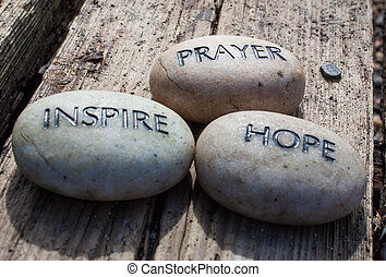 large round stones written with the words hope, prayer and inspire in bold black lettering.