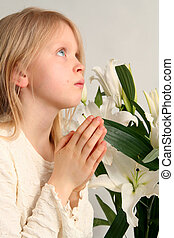 Prayer - Little girl praying on the easter lilies background
