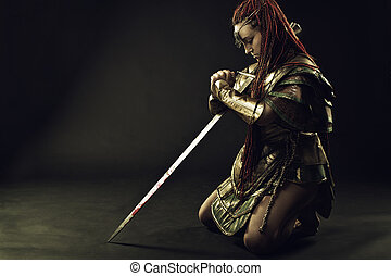 Prayer of warrior - Girl in armor standing on her knees with...