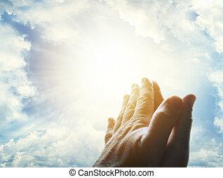 Prayer - Hands together praying in bright sky