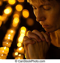 Prayer praying in Catholic church near candles. Religion concept.