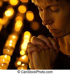 Prayer praying in Catholic church near candles. Religion...
