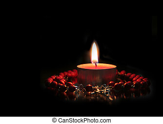Prayer - Red Candle and rosary against black (focus on the...