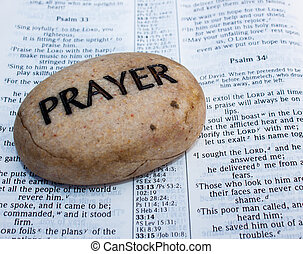 a beige rock with the word prayer written on it in bold black letters sitting on an open bible.