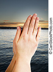 Prayer - Praying hands with a landscape with the ocean and a...