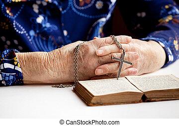 Prayer - An elderly pair of hands holding a cross