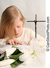 Prayer - Little girl reading holy bible and easter lilies...