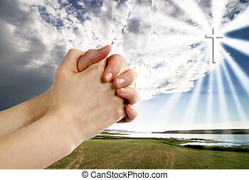 A pair of hands in a praying position set against a beautiful prairie lake landscape with a cross in the sky on the right side.