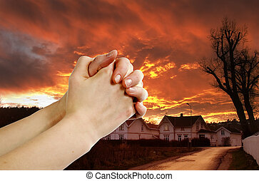 Hands praying with a dramatic red sky overa small town; prayer warrior.