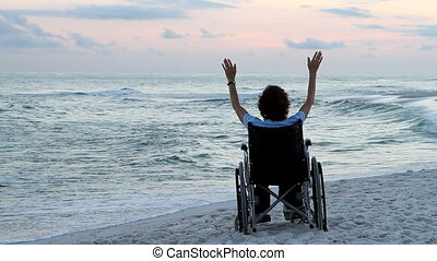 Prayer Wheelchair Beach - Lonely disabled woman sits and...
