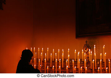 Prayer - Woman praying with candles.