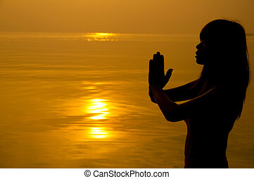 Woman with hands folded at seaside during sunset.