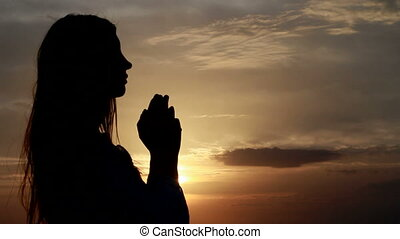 Prayer. Woman with hands folded at seaside during sunset.