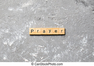 PRAYER word written on wood block. PRAYER text on cement table for your desing, concept