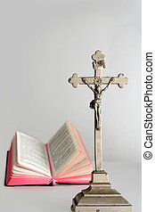 Prayerbook - Opened prayerbook and old cross on a white...
