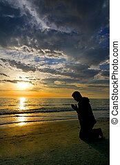 Prayers at the Ocean - A man kneeling and praying on the...