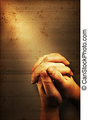 Prayers hands and sunbeam on old nostalgic background