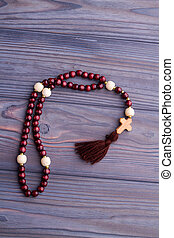 Prayer's rosary with red beads and wooden cross.