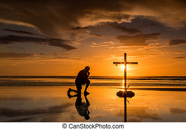 Prayful Cross Sunset - Man knelling by a cross with a crown...
