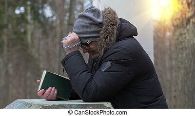 praying at outdoor near pedestal