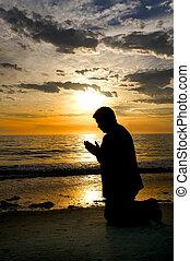 Praying at the Sea - A beautiful silhouette of a man praying...