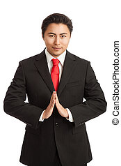 Praying businessman in red tie