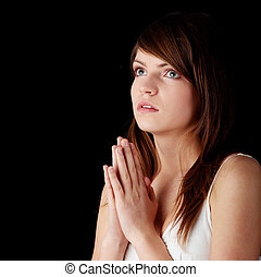 Closeup portrait of a young caucasian girl praying isolated on black background