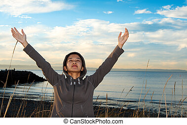 Praying girl - A girl with her hands up praying and...