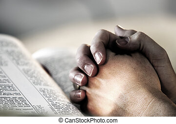 A man's hands clasped in prayer over a Holy Bible (shallow focus).