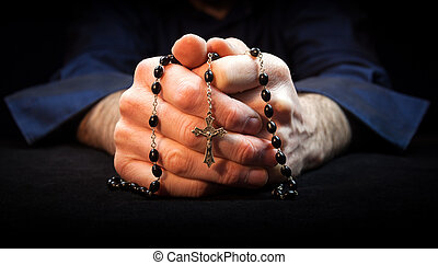 Praying Hands - Hands holding rosary beads and cross while...