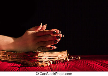 Praying hands on bible and rosary.