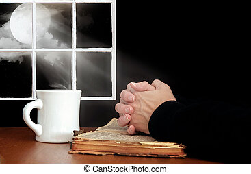 praying hands on old Bible