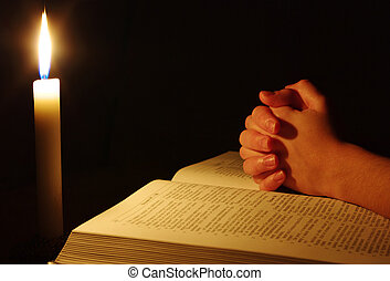 Praying hands on  open bible