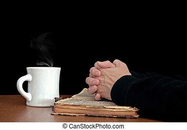 praying hands on worn Bible