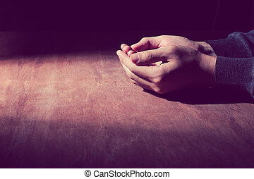 The open praying hands on the wooden desk background.