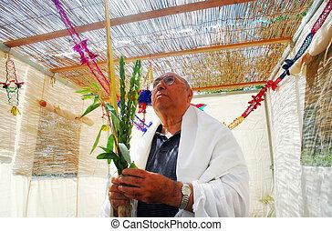 Praying in Sukkah for Jewish Holiday Sukkot - A Jewish man...
